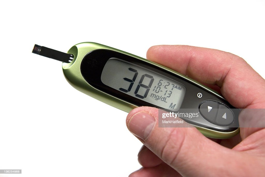 Glucose monitor displaying 38mg/dL being held by a person : Stock Photo