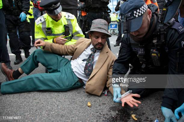 Glued on protester has his hand freed by police during Extinction Rebellion disruption outside City Airport on 10th October 2019 in London England...