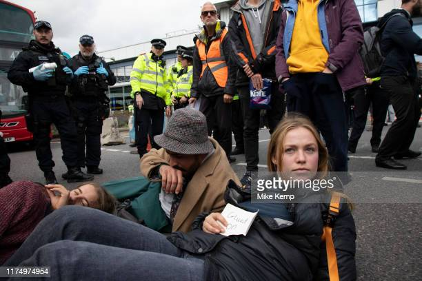 Glued on protesters during Extinction Rebellion disruption outside City Airport on 10th October 2019 in London England United Kingdom The protest is...