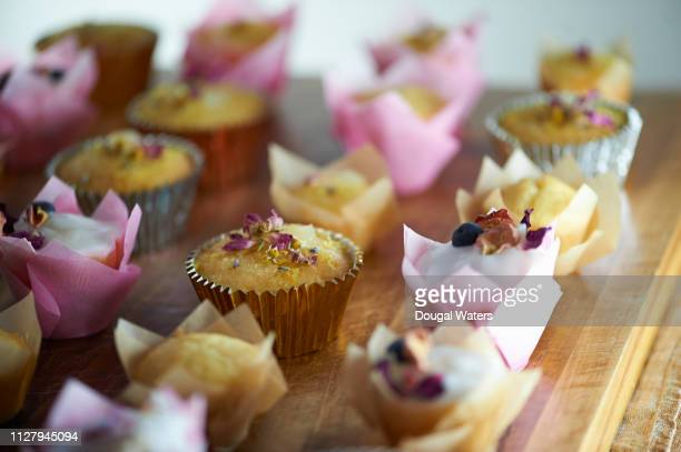 gluten free cup cakes decorated with edible flowers. - cake stock pictures, royalty-free photos & images