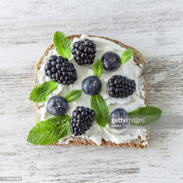 gluten free whole grain bread with vegan cream cheese, berries and mint - cream cheese stock pictures, royalty-free photos & images
