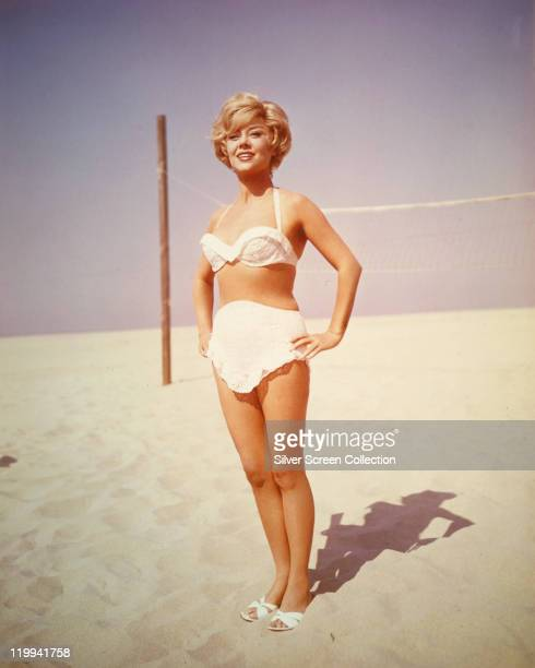 Glynis Johns South Africanborn British actress poses in a white bathing costume on the beach a volleyball net set up behind her circa 1960