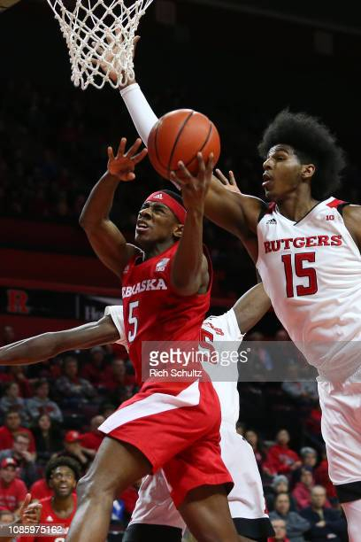 Glynn Watson Jr #5 of the Nebraska Cornhuskers attempts a layup as Issa Thiam and Myles Johnson of the Rutgers Scarlet Knights defend during the...