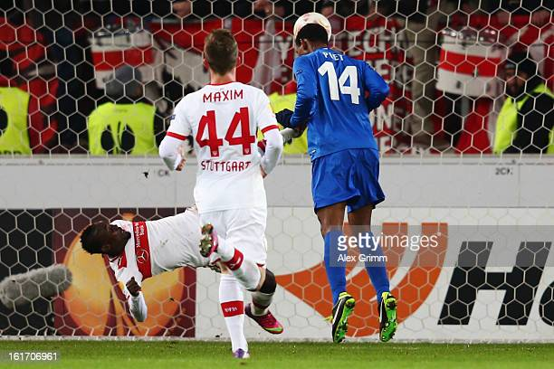 Glynor Plet of Genk scores his team's first goal against Arthur Boka and Alexandru Maxim of Stuttgart during the UEFA Europa League Round of 32 first...