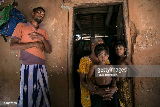 Gnanaseelan stands near his son Rajani with his grandmother Indra Devi and cousin Luxshagini outside their house in Mullaitivu Sri Lanka July 9 2013...