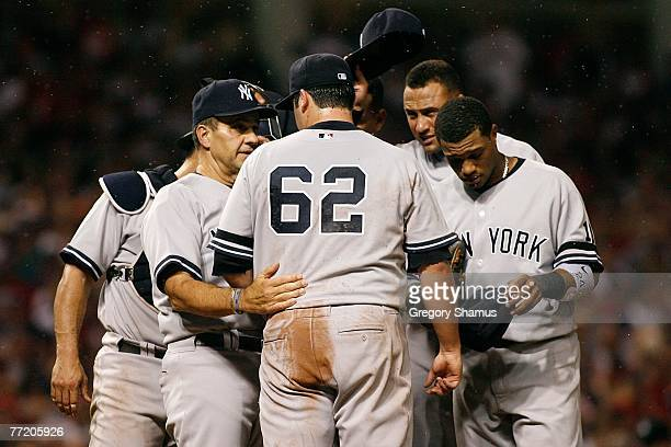Gnats swarn the mound as manager Joe Torre of the New York Yankees talks with relief pitcher Joba Chamberlain as his teammates try to swat the...