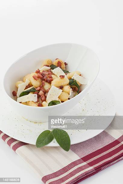 Gnocchi and bacon with napkin on white background