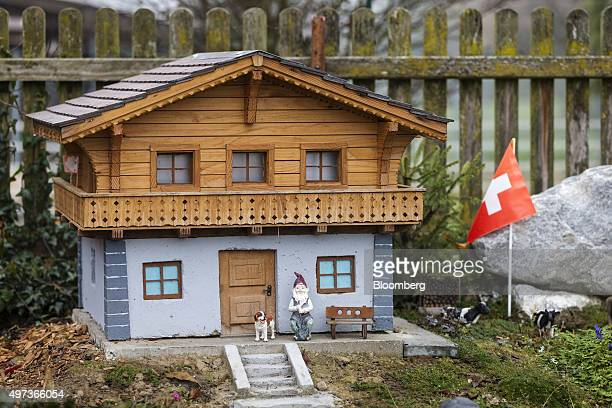 A gnome figurine and Swiss national flag sit by a miniature traditional Swiss residential house in Nebikon Switzerland on Thursday Nov 12 2015 Risks...