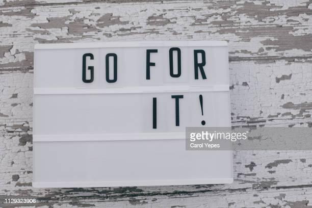 go  for  it message in lightbox. wooden background. - prazo imagens e fotografias de stock
