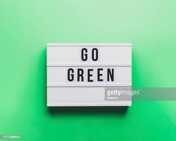 go green sign. green background. - activista fotografías e imágenes de stock