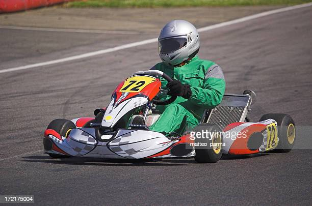 A go kart and driver racing round a track