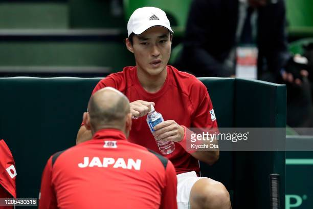 Go Soeda of Japan listens to team captain Satoshi Iwabuchi of Japan in his singles match against Emilio Gomez of Ecuador on day one of the Davis Cup...