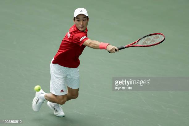 Go Soeda of Japan plays a backhand in his singles match against Emilio Gomez of Ecuador on day one of the Davis Cup qualifier between Japan and...