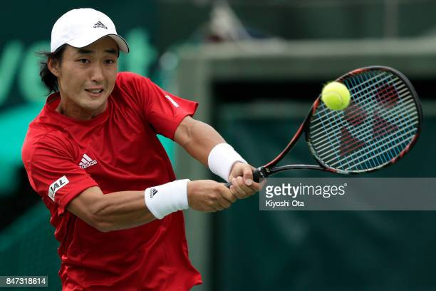 Go Soeda of Japan plays a backhand in his singles match against Thiago Monteiro of Brazil during day one of the Davis Cup World Group Playoff between...