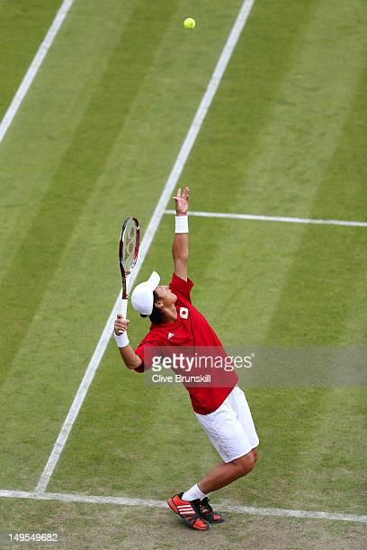 Go Soeda of Japan serves next to his partner Kei Nishikori of Japan during their Men's Doubles Tennis match against Stanislas Wawrinka and Roger...