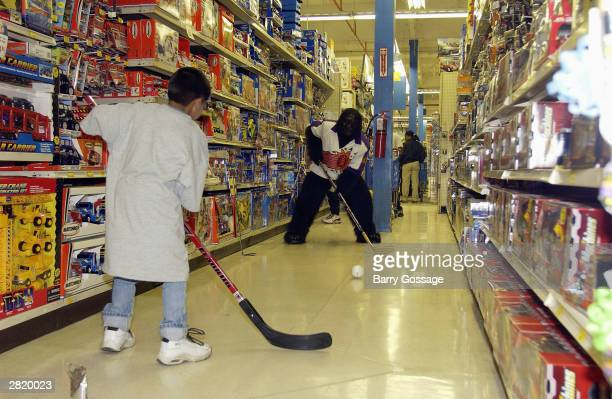 Go the Gorilla mascot of the Phoenix Suns plays floor hockey in the aisle with a young boy as the Suns help children of the Salvation Army with their...