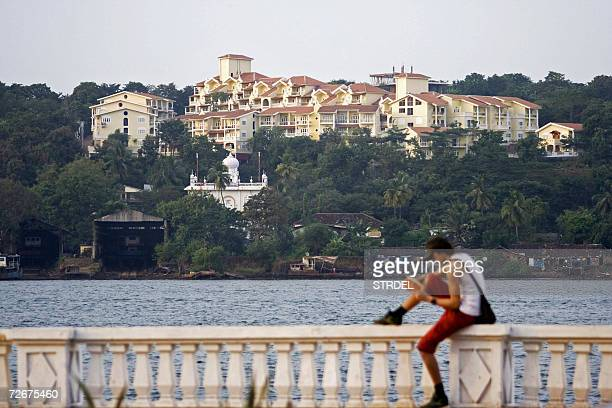 TO GO WITH STORY IndiaenvironmentGoa A lone tourist reads from a book on the banks of the river Mandovi with a new construction looming large on the...