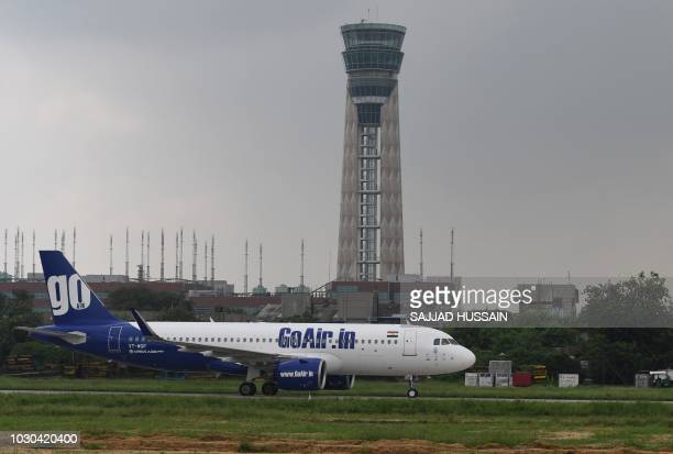 A GoAir plane taxis past a control tower at Indira Gandhi International Airport in New Delhi on September 10 2018