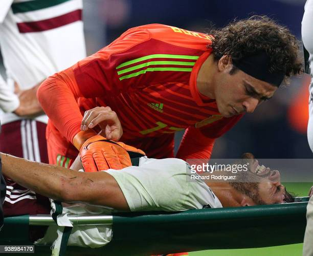 Goakeeper Guillermo Ochoa of Mexico talks to teammate Nestor Araujo of Mexico as he was taken off the field during the first half of an intenational...