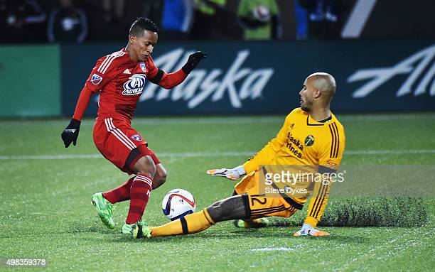 Goal keeper Adam Kwarasey of Portland Timbers slides in on Michael Barrios of FC Dallas during the second half of the match at Providence Park on...
