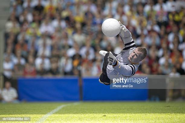 goal keeper diving for ball in stadium - goalkeeper stock pictures, royalty-free photos & images