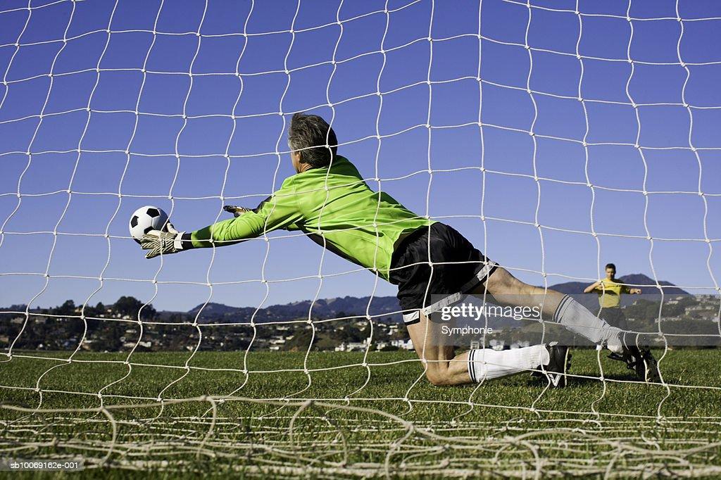 Goal keeper diving for ball : Stockfoto