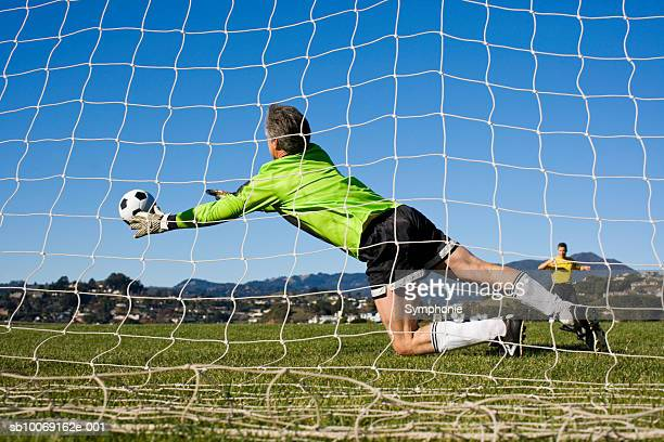 Goal keeper diving for ball