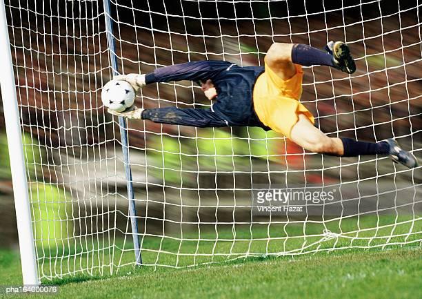 Goal keeper, horizontal, saving ball during match, full length