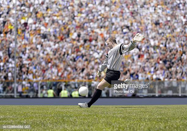 goal keeper kicking ball in stadium - goalkeeper stock pictures, royalty-free photos & images