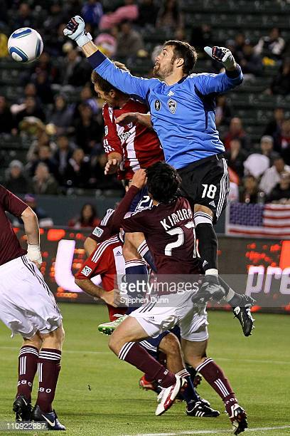 Goal keeper Matt Pickens of the Colorado Rapids jumps to bat the ball away from Jimmy Conrad of Chivas USA in front of Rapids defender Kosuke Kimura...