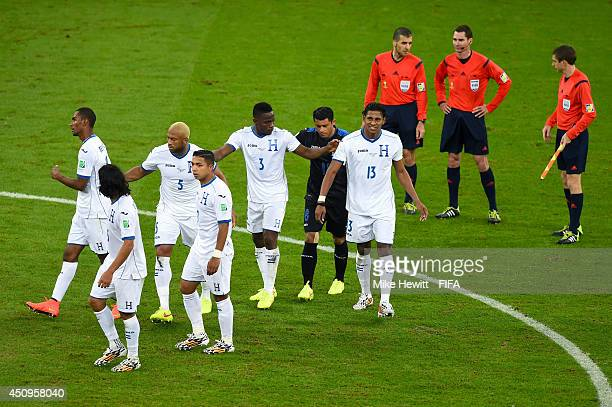 Goal keeper Noel Valladares of Honduras urges his teammates to stop protesting to referee Benjamin Williams at half time during the 2014 FIFA World...