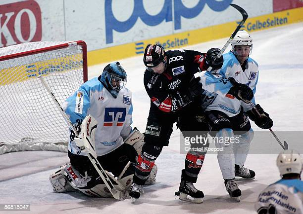 Goal keeper Roman Chechmanek of the Freezers and Paul Manning of the Freezers tackle Mika Puhakka of the Fuechse during the DEL Bundesliga game...