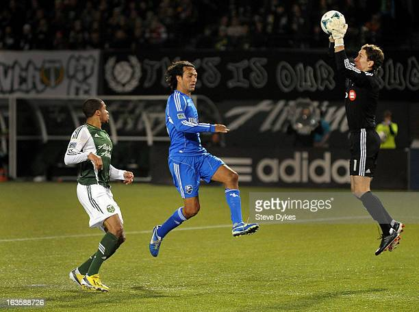 Goal keeper Troy Perkins of Montreal Impact grabs the ball as Ryan Johnson of Portland Timbers and Alessandro Nesta of Montreal Impact close in...