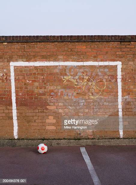 Goal posts painted on playground wall, football on ground