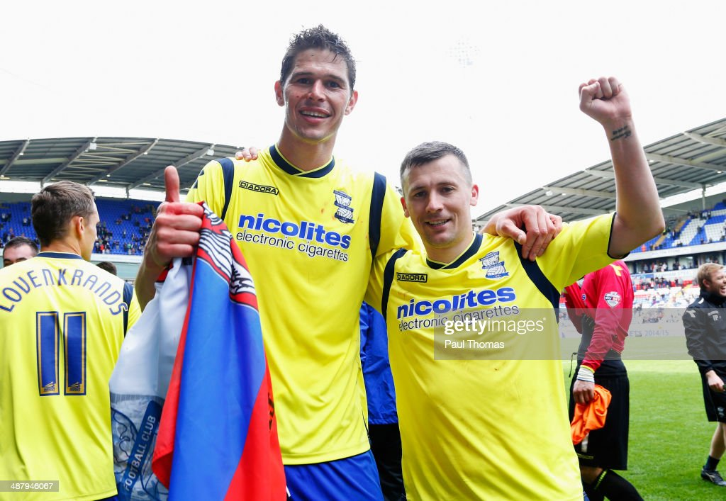 Goal scorers Nikola Zigic (L) and Paul Caddis of Birmingham City celebrate as they avoid relegation after the Sky Bet Championship match between Bolton Wanderers and Birmingham City at Reebok Stadium on May 3, 2014 in Bolton, England.