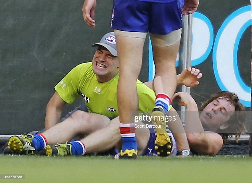 Goal umpire Courtney Lai lies on the ground after injuring his knee after he was struck by Liam Picken of the Bulldogs during the round two AFL match between the Western Bulldogs and the Fremantle Dockers at Etihad Stadium on April 6, 2013 in Melbourne, Australia.