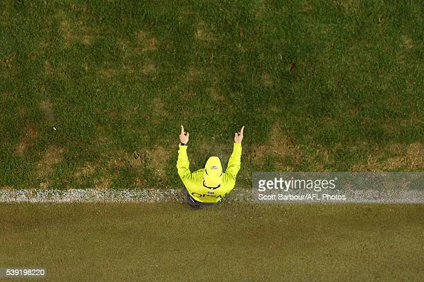 A goal umpire signals as the Hawks kick a goal during the round 12 AFL match between the Essendon Bombers and the Hawthorn Hawks at Etihad Stadium on...