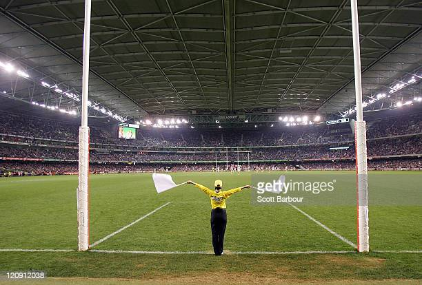 A goal umpire waves his flags as he signals a goal during the round 21 AFL match between the St Kilda Saints and the Collingwood Magpies at Etihad...