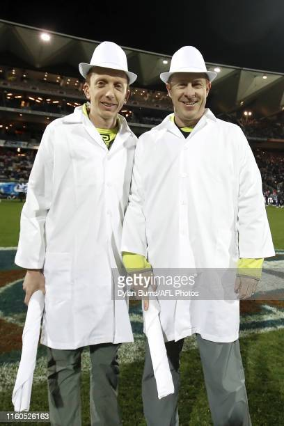 Goal Umpires Chris Appleton and Dylan Benwell pose for a photo in their white coats and hats for retro round during the 2019 AFL round 21 match...