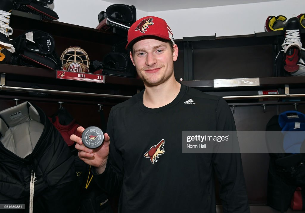 Goalie Adin Hill #31 of the Arizona Coyotes holds a game puck following a 4-3 shootout victory against the Los Angeles Kings at Gila River Arena on March 13, 2018 in Glendale, Arizona. It was Hill's first career NHL win.
