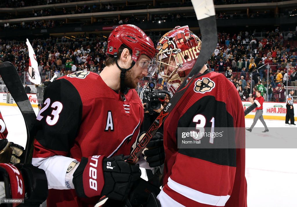 Goalie Adin Hill #31 of the Arizona Coyotes is congratulated by teammate Oliver Ekman-Larsson #23 after a 4-3 shootout victory against the Los Angeles Kings at Gila River Arena on March 13, 2018 in Glendale, Arizona. It was Hill's first career NHL win.