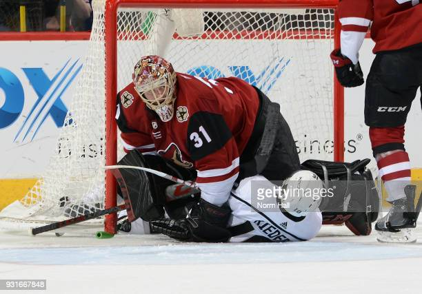 Goalie Adin Hill of the Arizona Coyotes lays on top of Tobias Rieder of the Los Angeles Kings after Rieder slid into the net during the second period...