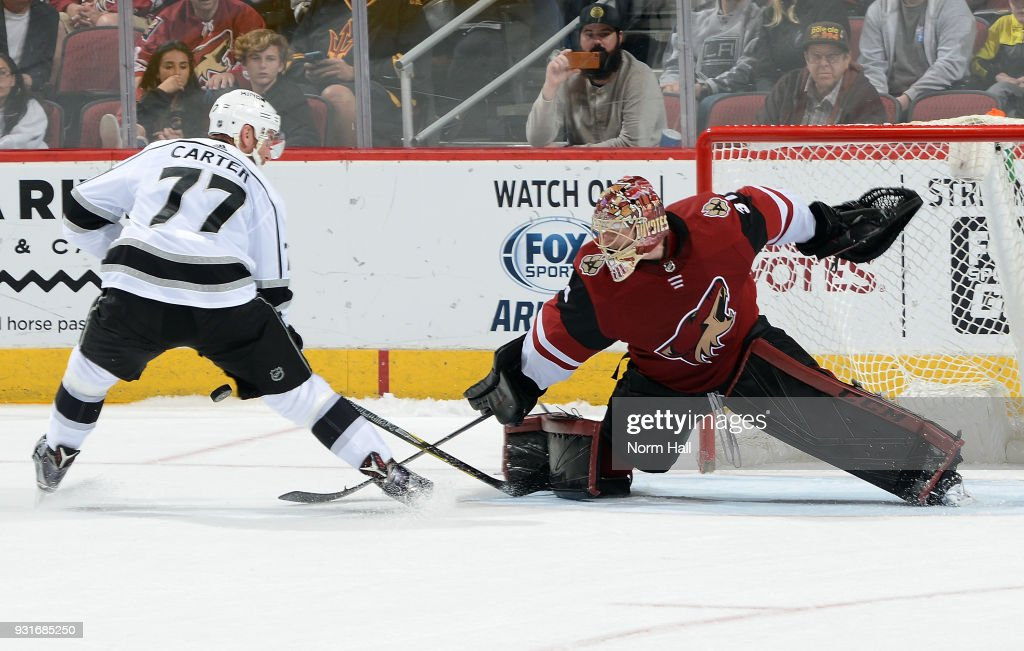Goalie Adin Hill #31 of the Arizona Coyotes makes a save on the shot by Jeff Carter #77 of the Los Angeles Kings during the overtime shootout at Gila River Arena on March 13, 2018 in Glendale, Arizona.