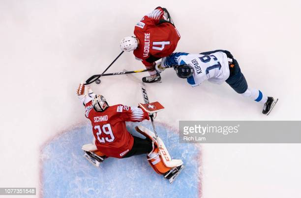Goalie Akira Schmid of Switzerland reaches out to cover up the puck as Rasmus Kupari of Finland and Simon Le Coultre of Switzerland battle in...