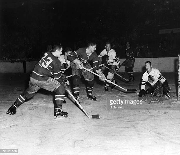 Goalie Al Rollins of the Chicago Blackhawks makes the save on Jean Beliveau of the Montreal Canadiens as Claude Provost of the Canadiens and Frank...