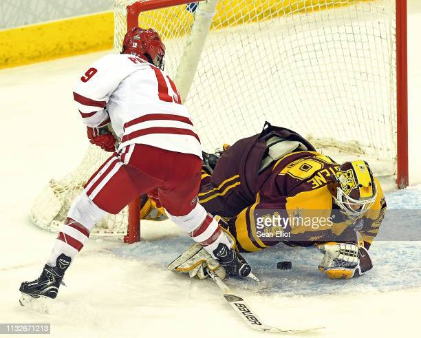 Goalie Alex Gulstene of the Minnesota Golden Gophers dives to cover the puck as she makes a save on the driving Annie Pankowski of the Wisconsin...