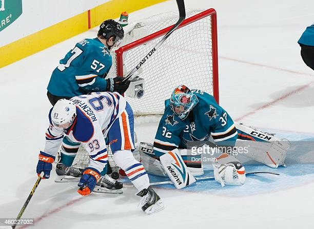 Goalie Alex Stalock and Tommy Wingels of the San Jose Sharks defend the net against Ryan NugentHopkins of the Edmonton Oilers during an NHL game on...