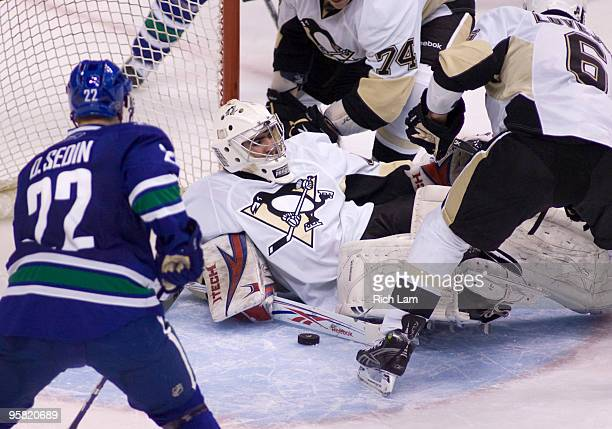 Goalie Alexander Pechurski of the Pittsburgh Penguins tries cover the loose puck while teammates Ben Lovejoy and Jay McKee and Daniel Sedin of the...