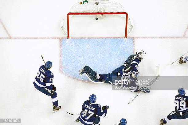 Goalie Anders Lindback of the Tampa Bay Lightning misses the puck allowing the first goal for the Toronto Maple Leafs during the first period of the...