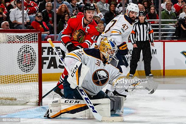 Goalie Anders Nilsson of the Buffalo Sabres gloves the puck as Jonathan Toews of the Chicago Blackhawks and Zach Bogosian watch from behind in the...